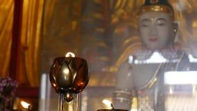 Flamma från den brinnande oljastearinljuslampan i buddistisk tempel closeup 4K stock video