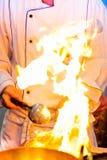 Flamma matlagning, brandbrännskada lagar mat på järnpannan, kock i restaur royaltyfria bilder