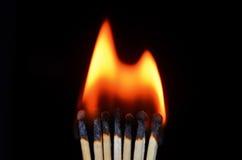 Flamma och match på den svarta bakgrunden Arkivfoto