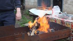 Flamma som stiger från brinnande trä och kol i ett mangal i trädgården stock video