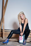 Flammable fashion woman. Fashion concept image.  Beautiful blond woman sitting on can of Flammable liquid Royalty Free Stock Image