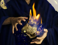 Flammable paper wad in hands of magician. Flammable paper wad with lettering Burning spell in hands of magician wearing dark clothes. alchemy science background Royalty Free Stock Images