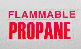 Flammable Propane. Sign of flammable propane is on a white metal container. Sign is a slight fade due to weathering Stock Photos
