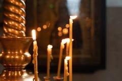 Flamman av kyrkastearinljus som tänds i kyrkan arkivbild