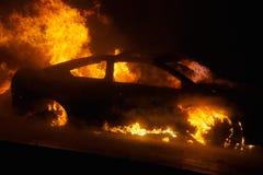 Flammande bilbrand på natten Arkivbild