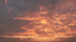 Flammande himmel med apelsinen fördunklar på solnedgången royaltyfri foto