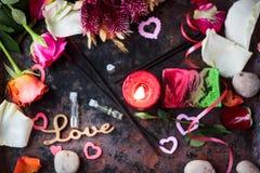 Flammande stearinljus och liten doftflaska på svart yttersida Royaltyfri Foto