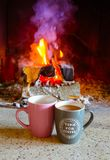 Flamme colorée lumineuse, bois brûlant à la cheminée, café deux Images libres de droits