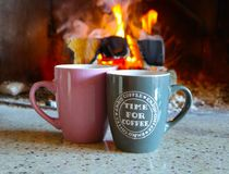 Flamme colorée lumineuse, bois brûlant à la cheminée, café deux Photo stock