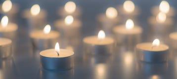 Flamme de beaucoup de bougies brûlant sur la couleur de bleu de fond Photo stock