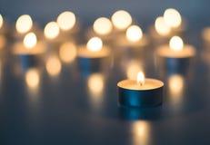 Flamme de beaucoup de bougies brûlant sur la couleur de bleu de fond Image stock