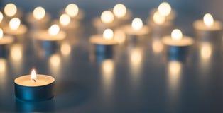 Flamme de beaucoup de bougies brûlant sur la couleur de bleu de fond Photos stock