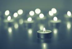 Flamme de beaucoup de bougies brûlant sur la couleur de bleu de fond Images stock