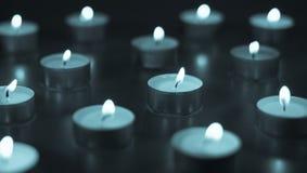 Flamme de beaucoup de bougies brûlant sur la couleur de bleu de fond Photo libre de droits
