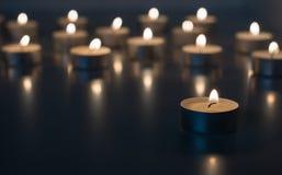 Flamme de beaucoup de bougies brûlant sur la couleur de bleu de fond Image libre de droits