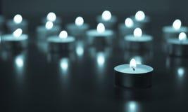 Flamme de beaucoup de bougies brûlant sur la couleur de bleu de fond Photographie stock