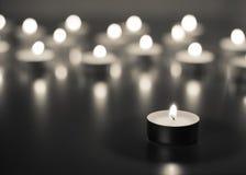Flamme de beaucoup de bougies brûlant sur la couleur de monohrome de fond Images stock