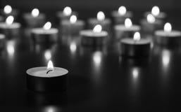 Flamme de beaucoup de bougies brûlant sur la couleur de monohrome de fond Photographie stock