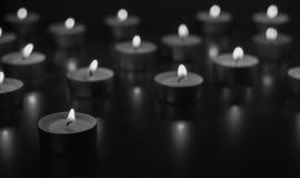 Flamme de beaucoup de bougies brûlant sur la couleur de monohromt de fond Photo stock