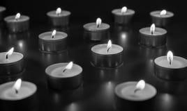 Flamme de beaucoup de bougies brûlant sur la couleur de monohromt de fond Photographie stock libre de droits