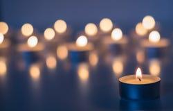 Flamme de beaucoup de bougies brûlant sur la couleur de violette de fond Photos stock