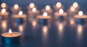 Flamme de beaucoup de bougies brûlant sur la couleur de violette de fond Image stock