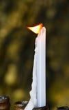 Flamme der weißen schmelzenden Kerze im Tempel oder in der Kirche Stockbild