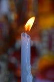 Flamme der weißen schmelzenden Kerze im Tempel oder in der Kirche Lizenzfreie Stockbilder