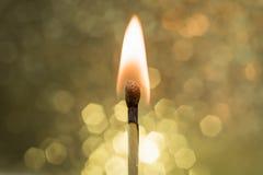 Flamme des brennenden Zündholzes mit Gold-Bokeh-Hintergrund lizenzfreie stockfotografie
