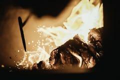Flamme du feu de flamme en four, poussant le bâton et les étincelles photo stock