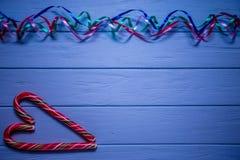 Flamme multicolore sur le fond en bois bleu avec la sucrerie rouge avec le symbole de coeur Images stock