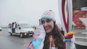 Flamme olympique de course de relais dans le St Petersbourg en octobre Le porteur de flambeau féminin donnent l'entrevue émotions banque de vidéos