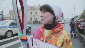 Flamme olympique de course de relais dans le St Petersbourg en octobre Le porteur de flambeau féminin donnent l'entrevue Sourire banque de vidéos