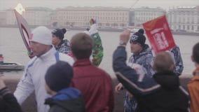 Flamme olympique de course de relais dans le St Petersbourg en octobre Porteur de flambeau courant sur le bord de mer Les gens banque de vidéos