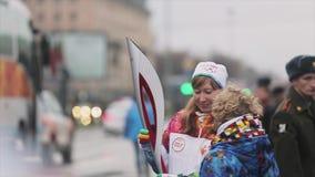Flamme olympique de course de relais dans le St Petersbourg Le porteur de flambeau féminin se préparent au fonctionnement banque de vidéos