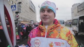 Flamme olympique de course de relais dans le St Petersbourg Le porteur de flambeau masculin donnent l'entrevue Les gens Vecteur d banque de vidéos