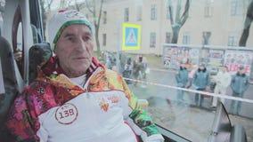Flamme olympique de course de relais dans le St Petersbourg Le porteur de flambeau retiré donnent l'entrevue en conduisant l'auto banque de vidéos