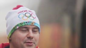 Flamme olympique de course de relais dans le St Petersbourg Le portrait du porteur de flambeau de mâle adulte donnent l'entrevue banque de vidéos