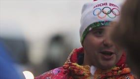 Flamme olympique de course de relais dans le St Petersbourg Le portrait du porteur de flambeau masculin donnent l'entrevue émotio banque de vidéos