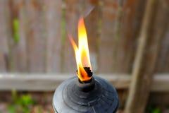 Flamme von Metall-Tiki-Fackel gegen unscharfen Bretterzaun lizenzfreie stockfotografie