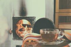 Flammen des Feuers in einem Kamin und in einer Tasse Tee Stockbild