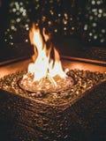 Flammen in einer Feuergrube mit Glasfelsen lizenzfreie stockbilder