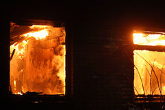Flammes à l'intérieur de maison sur le feu. Image stock