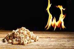 Flammes brûlant derrière un tas des granules en bois Photo stock