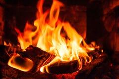 Flammes dans la cheminée, dans le bois de chauffage de premier plan images stock