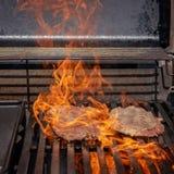 Flammes sur le bifteck sur un BBQ photographie stock