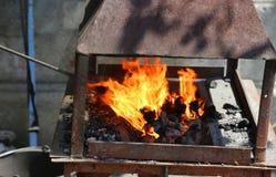 Flammes sur les charbons chauds Photos stock