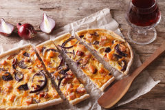 Flammkuchen sliced pie and red wine close-up. horizontal Stock Images