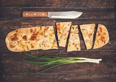 Flammkuchen or Traditional Alsatian Pie, Tart Flambe, Green Onio. Ns and Knife on Rustic Wooden Background. Retro Styled Food Background Stock Image