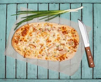 Flammkuchen or Traditional Alsatian Pie, Tart Flambe, Green Onio. Ns and Knife on Shabby Chic Vintage Wooden Background. Retro Styled Food Background Stock Photos
